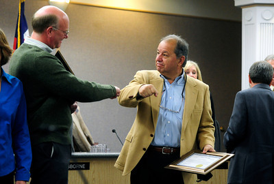 COUNCIL Tim Plass, left, gets a fist bump from George Karakehian after the swearing-in ceremony of the new Boulder city council on Tuesday.   PHOTO BY MARTY CAIVANO Nov. 15, 2011