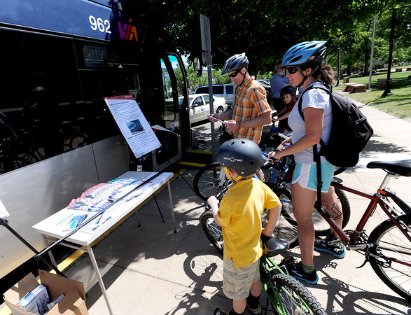 """Matt McKay, stops to check out the new NABI RTD bus with his wife, Tamara, son, Mason and  older son, Ryland, seen  in the background<br /> For a video of the bus, go to  <a href=""""http://www.dailycamera.com"""">http://www.dailycamera.com</a>.<br /> Cliff Grassmick / June 6, 2012"""