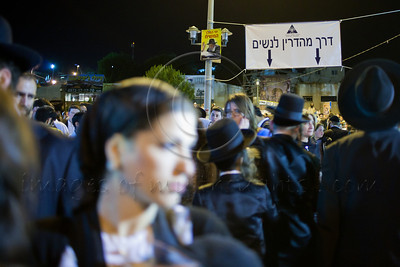 A sign indicates a separate path for women for the meticulously observant as hundreds of thousands celebrate the Jewish holiday of Lag BaOmer at the gravesite of Rabbi Shimon Bar Yochai. Meron, Israel. 22/05/2011.