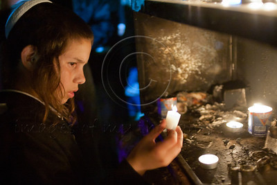 A young boy lights candles as hundreds of thousands celebrate the Jewish holiday of Lag BaOmer at the gravesite of Rabbi Shimon Bar Yochai. Meron, Israel. 22/05/2011.