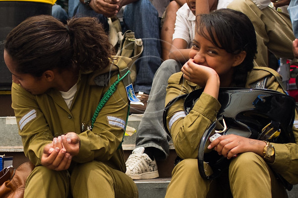 """Two female Ethiopian IDF soldiers at a memorial service for 4,000 Ethiopian Jews held at Mount Hertzel, symbolically coinciding with Jerusalem Reunification Day. Jerusalem, Israel. 01/06/2011.<br /> <br /> The Ethiopian Jewish community, called Beta-Israel, lived in seclusion for over 1,000 years, only reconnecting to the Jewish world in the late 20th century. According to Ethiopian tradition, their roots go back 3,000 years to the era of King Solomon. Like their brethren in many parts of the world, Ethiopian Jews suffered persecution for their beliefs and refusal to adopt Christianity. In the Middle Ages their lands were confiscated, villages plundered and many murdered. They were nicknamed Falash - intruders, homeless and without property. The Ethiopian Jewish community, living for so long in complete seclusion, were convinced they were the last Jews left on the face of the Earth. They practiced all the religious rituals with which they were familiar including male circumcision on the eight day from birth, Kashrut (Kosher) rules dealing with food, the holiness of the Sabbath and they prayed, three times a day, facing the holy city of Jerusalem, yearning to return.<br /> <br /> In 1975 Israel formally recognized """"Beita Israel"""" as a part of the Jewish nation. In 1977 Israeli PM Menachem Begin instructed the government to bring them home. The Ethiopian government refused to release them and millions of dollars were transferred to the government of Sudan for them to be allowed refugee status in its territory. The rumor spread quickly to villages all over Ethiopia – a route to Jerusalem via Sudan. Thousands left their homes overnight and set out on a long and dangerous journey to Sudan through unbearable desert heat, thirst and hunger, avoiding bandits and the Ethiopian military. They left everything they had behind. They were walking towards fulfillment of a thousands of years old dream – reuniting with Jerusalem.<br /> <br /> Refugee camps in Sudan were of horrible c"""