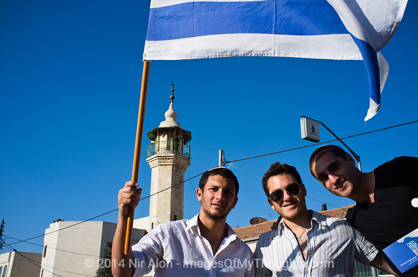 Three young Jewish Israelis pose for a photo near the Sheik Jarrah mosque. Jerusalem, Israel. 1 June 2011.<br /> <br /> Rejoicing the 44th anniversary of the reunification of Jerusalem, they descended on the city from all over the country coming to demonstrate their love and commitment to Israel's capital. Starting out in Sheikh Jarrah, or  Shimon HaTzadik as they call it, participants were met by left-wing activists demonstrating in solidarity with the Arab residents of the neighborhood. Right-wing MK Michael Ben-Ari and activist Itamar Ben-Gvir supplied the spark necessary for combustion and indeed some violence erupted ending with at least two Solidarity protestors arrested.                                  The Dance of Flags March continued through the Damascus Gate and Muslim Quarter to the Western Wall where a festive rally was held.