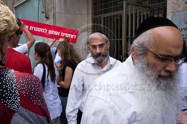 "Religious Jews exit the Rabbinical Court in contempt of protesters against religious coercion and the monopoly of the Rabbinate in Israel over matters of marriage and divorce. Jerusalem, Israel. 9 June 2011. <br /> <br /> The Rabbinical Courts are part of the Israeli judicial system. They pass sentence based on Jewish 'Halacha' and have exclusive authority in matters of marriage and divorce for Jews in the State of Israel and some authority in matrimonial law including relevant issues in conversion to Judaism. The authority of the Rabbinical Courts is based on legislation in the Israeli Knesset and influenced by a 63-year balance of political power between secular Israelis and religious parties. Jewish marriage in Israel is not recognized unless performed by the Rabbinate and Israeli Jews cannot divorce outside of the Rabbinate. These facts have an enormous effect on many aspects of the private lives of secular Jews who would prefer to be governed by civilian marriage laws. Jews in Israel are held hostage by laws of 'Halacha' whether they believe in them or not - religious coercion, in what some believe, its darkest form.<br /> <br /> Recently, grassroots movements have begun to deal with these issues. The Israel Religious Action Center of the Israel Movement for Progressive Judaism, represented by Motti Bebchuk, and Free Israel, represented by Eyal Akerman, joined hands today to demonstrate in Jerusalem against the monopoly the Rabbinate has over matrimonial law in Israel. Dressed up as brides and grooms and carrying a Chuppah - a canopy under which a Jewish couples stand during their wedding ceremony, activists chained themselves to each other and to Rabbinical Court doors symbolizing the tight grip of the Rabbinate. Their slogan is ""We Are Being Squeezed Into One Frame"" emphasizing the absence of choice."