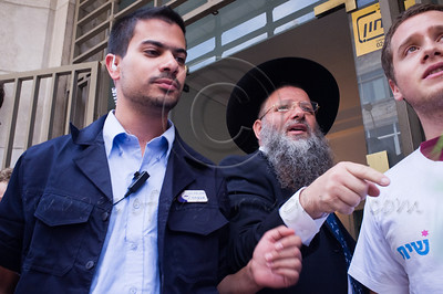 "Angry religious Jew rebukes protesters against religious coercion and the monopoly of the Rabbinate in Israel over matters of marriage and divorce. Jerusalem, Israel. 9 June 2011.   The Rabbinical Courts are part of the Israeli judicial system. They pass sentence based on Jewish 'Halacha' and have exclusive authority in matters of marriage and divorce for Jews in the State of Israel and some authority in matrimonial law including relevant issues in conversion to Judaism. The authority of the Rabbinical Courts is based on legislation in the Israeli Knesset and influenced by a 63-year balance of political power between secular Israelis and religious parties. Jewish marriage in Israel is not recognized unless performed by the Rabbinate and Israeli Jews cannot divorce outside of the Rabbinate. These facts have an enormous effect on many aspects of the private lives of secular Jews who would prefer to be governed by civilian marriage laws. Jews in Israel are held hostage by laws of 'Halacha' whether they believe in them or not - religious coercion, in what some believe, its darkest form.  Recently, grassroots movements have begun to deal with these issues. The Israel Religious Action Center of the Israel Movement for Progressive Judaism, represented by Motti Bebchuk, and Free Israel, represented by Eyal Akerman, joined hands today to demonstrate in Jerusalem against the monopoly the Rabbinate has over matrimonial law in Israel. Dressed up as brides and grooms and carrying a Chuppah - a canopy under which a Jewish couples stand during their wedding ceremony, activists chained themselves to each other and to Rabbinical Court doors symbolizing the tight grip of the Rabbinate. Their slogan is ""We Are Being Squeezed Into One Frame"" emphasizing the absence of choice."