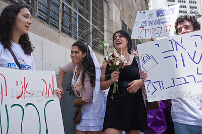 "Grassroots movements protest religious coercion and the monopoly of the Rabbinate in Israel over matters of marriage and divorce. Jerusalem, Israel. 9 June 2011.   The Rabbinical Courts are part of the Israeli judicial system. They pass sentence based on Jewish 'Halacha' and have exclusive authority in matters of marriage and divorce for Jews in the State of Israel and some authority in matrimonial law including relevant issues in conversion to Judaism. The authority of the Rabbinical Courts is based on legislation in the Israeli Knesset and influenced by a 63-year balance of political power between secular Israelis and religious parties. Jewish marriage in Israel is not recognized unless performed by the Rabbinate and Israeli Jews cannot divorce outside of the Rabbinate. These facts have an enormous effect on many aspects of the private lives of secular Jews who would prefer to be governed by civilian marriage laws. Jews in Israel are held hostage by laws of 'Halacha' whether they believe in them or not - religious coercion, in what some believe, its darkest form.  Recently, grassroots movements have begun to deal with these issues. The Israel Religious Action Center of the Israel Movement for Progressive Judaism, represented by Motti Bebchuk, and Free Israel, represented by Eyal Akerman, joined hands today to demonstrate in Jerusalem against the monopoly the Rabbinate has over matrimonial law in Israel. Dressed up as brides and grooms and carrying a Chuppah - a canopy under which a Jewish couples stand during their wedding ceremony, activists chained themselves to each other and to Rabbinical Court doors symbolizing the tight grip of the Rabbinate. Their slogan is ""We Are Being Squeezed Into One Frame"" emphasizing the absence of choice."