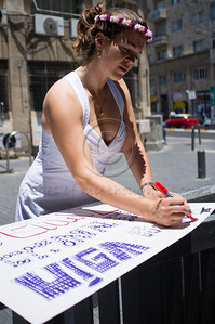 "Female activist dressed as a bride prepares a sign for protest of religious coercion and the monopoly of the Rabbinate in Israel over matters of marriage and divorce. Jerusalem, Israel. 9 June 2011.   The Rabbinical Courts are part of the Israeli judicial system. They pass sentence based on Jewish 'Halacha' and have exclusive authority in matters of marriage and divorce for Jews in the State of Israel and some authority in matrimonial law including relevant issues in conversion to Judaism. The authority of the Rabbinical Courts is based on legislation in the Israeli Knesset and influenced by a 63-year balance of political power between secular Israelis and religious parties. Jewish marriage in Israel is not recognized unless performed by the Rabbinate and Israeli Jews cannot divorce outside of the Rabbinate. These facts have an enormous effect on many aspects of the private lives of secular Jews who would prefer to be governed by civilian marriage laws. Jews in Israel are held hostage by laws of 'Halacha' whether they believe in them or not - religious coercion, in what some believe, its darkest form.  Recently, grassroots movements have begun to deal with these issues. The Israel Religious Action Center of the Israel Movement for Progressive Judaism, represented by Motti Bebchuk, and Free Israel, represented by Eyal Akerman, joined hands today to demonstrate in Jerusalem against the monopoly the Rabbinate has over matrimonial law in Israel. Dressed up as brides and grooms and carrying a Chuppah - a canopy under which a Jewish couples stand during their wedding ceremony, activists chained themselves to each other and to Rabbinical Court doors symbolizing the tight grip of the Rabbinate. Their slogan is ""We Are Being Squeezed Into One Frame"" emphasizing the absence of choice."