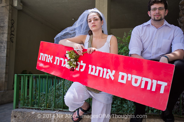 "Grassroots movements protest religious coercion and the monopoly of the Rabbinate in Israel over matters of marriage and divorce with slogan ""We are being squeezed into one frame"". Jerusalem, Israel. 9 June 2011. <br /> <br /> The Rabbinical Courts are part of the Israeli judicial system. They pass sentence based on Jewish 'Halacha' and have exclusive authority in matters of marriage and divorce for Jews in the State of Israel and some authority in matrimonial law including relevant issues in conversion to Judaism. The authority of the Rabbinical Courts is based on legislation in the Israeli Knesset and influenced by a 63-year balance of political power between secular Israelis and religious parties. Jewish marriage in Israel is not recognized unless performed by the Rabbinate and Israeli Jews cannot divorce outside of the Rabbinate. These facts have an enormous effect on many aspects of the private lives of secular Jews who would prefer to be governed by civilian marriage laws. Jews in Israel are held hostage by laws of 'Halacha' whether they believe in them or not - religious coercion, in what some believe, its darkest form.<br /> <br /> Recently, grassroots movements have begun to deal with these issues. The Israel Religious Action Center of the Israel Movement for Progressive Judaism, represented by Motti Bebchuk, and Free Israel, represented by Eyal Akerman, joined hands today to demonstrate in Jerusalem against the monopoly the Rabbinate has over matrimonial law in Israel. Dressed up as brides and grooms and carrying a Chuppah - a canopy under which a Jewish couples stand during their wedding ceremony, activists chained themselves to each other and to Rabbinical Court doors symbolizing the tight grip of the Rabbinate. Their slogan is ""We Are Being Squeezed Into One Frame"" emphasizing the absence of choice."