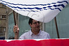 "Activist carries a Chuppah in protest against religious coercion and the monopoly of the Rabbinate in Israel over matters of marriage and divorce. Jerusalem, Israel. 9 June 2011. <br /> <br /> The Rabbinical Courts are part of the Israeli judicial system. They pass sentence based on Jewish 'Halacha' and have exclusive authority in matters of marriage and divorce for Jews in the State of Israel and some authority in matrimonial law including relevant issues in conversion to Judaism. The authority of the Rabbinical Courts is based on legislation in the Israeli Knesset and influenced by a 63-year balance of political power between secular Israelis and religious parties. Jewish marriage in Israel is not recognized unless performed by the Rabbinate and Israeli Jews cannot divorce outside of the Rabbinate. These facts have an enormous effect on many aspects of the private lives of secular Jews who would prefer to be governed by civilian marriage laws. Jews in Israel are held hostage by laws of 'Halacha' whether they believe in them or not - religious coercion, in what some believe, its darkest form.<br /> <br /> Recently, grassroots movements have begun to deal with these issues. The Israel Religious Action Center of the Israel Movement for Progressive Judaism, represented by Motti Bebchuk, and Free Israel, represented by Eyal Akerman, joined hands today to demonstrate in Jerusalem against the monopoly the Rabbinate has over matrimonial law in Israel. Dressed up as brides and grooms and carrying a Chuppah - a canopy under which a Jewish couples stand during their wedding ceremony, activists chained themselves to each other and to Rabbinical Court doors symbolizing the tight grip of the Rabbinate. Their slogan is ""We Are Being Squeezed Into One Frame"" emphasizing the absence of choice."