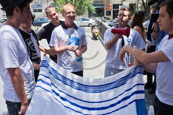 """Eyal Akerman (center L) and Motti Bebchuk (center R) give last-minute briefing for protest against religious coercion and the monopoly of the Rabbinate in Israel over matters of marriage and divorce. Jerusalem, Israel. 9 June 2011. <br /> <br /> The Rabbinical Courts are part of the Israeli judicial system. They pass sentence based on Jewish 'Halacha' and have exclusive authority in matters of marriage and divorce for Jews in the State of Israel and some authority in matrimonial law including relevant issues in conversion to Judaism. The authority of the Rabbinical Courts is based on legislation in the Israeli Knesset and influenced by a 63-year balance of political power between secular Israelis and religious parties. Jewish marriage in Israel is not recognized unless performed by the Rabbinate and Israeli Jews cannot divorce outside of the Rabbinate. These facts have an enormous effect on many aspects of the private lives of secular Jews who would prefer to be governed by civilian marriage laws. Jews in Israel are held hostage by laws of 'Halacha' whether they believe in them or not - religious coercion, in what some believe, its darkest form.<br /> <br /> Recently, grassroots movements have begun to deal with these issues. The Israel Religious Action Center of the Israel Movement for Progressive Judaism, represented by Motti Bebchuk, and Free Israel, represented by Eyal Akerman, joined hands today to demonstrate in Jerusalem against the monopoly the Rabbinate has over matrimonial law in Israel. Dressed up as brides and grooms and carrying a Chuppah - a canopy under which a Jewish couples stand during their wedding ceremony, activists chained themselves to each other and to Rabbinical Court doors symbolizing the tight grip of the Rabbinate. Their slogan is """"We Are Being Squeezed Into One Frame"""" emphasizing the absence of choice."""