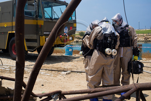 """Policemen in chemical protective suits deploy at the site of a passenger jet crash in """"Turning Point 5"""" exercise at Reading Power Plant. Tel-Aviv, Israel. 23rd June 2011."""