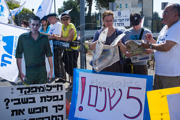 Mother Aviva Shalit reads newspaper headlines covering her son's five years in Hammas captivity outside the Prime Minister's Office. Jerusalem, Israel. 26th June 2011.