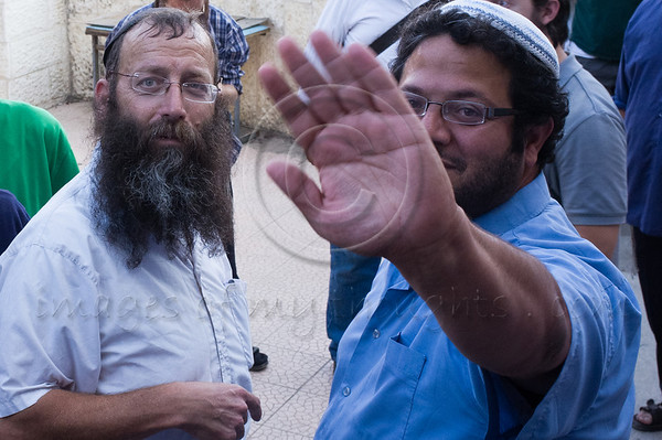 Itamar Ben-Gvir raises arm to block photograph while speaking with Baruch Marzel in Simon The Just (Shimon HaTzadik) neighborhood in Sheikh Jarrah.