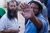 Itamar Ben-Gvir raises arm to block photograph while speaking with Baruch Marzel in Simon The Just (Shimon HaTzadik) neighborhood in Sheikh Jarrah.
