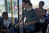 A young women boards bus 56 from the rear door and reaches for the self-service multi-ride ticket puncher hanging by a chain for women in the rear. Jerusalem, Israel. 13/07/2011.
