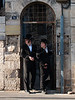Two young Haredi men watch rioters through a doorway. Jerusalem, Israel. 23/07/2011.