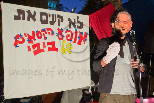 PM Netanyahu impersonator Ram Mizrachi pulls a stock-puppet of Finance Minister Yuval Steinitzout of his magician's hat in a comedy show at Tent City Menorah Park. Jerusalem, Israel. 26/07/2011.