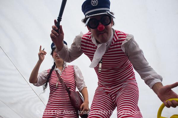 Clowns on stilts pretend to assault photographer at a summer beach party at the Malcha Mall. Jerusalem, Israel. 29/07/2011.