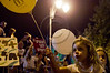 A young girl with yellow balloon is carried on her father's shoulders in a demonstration for social justice. Jerusalem, Israel. 30/07/2011.