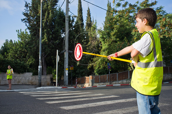 Sixth graders assist younger pupils crossing the road to Bet Hakerem Elementary School as almost two-million pupils return to school today nationwide. Jerusalem, Israel. 01/09/2011.