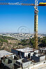 A tall crane looms over a housing construction site in Giloh. Jerusalem, Israel. 04/10/2011.
