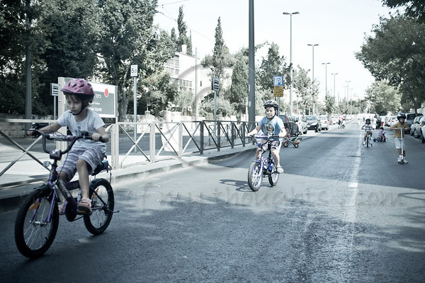 Yom Kippur is celebrated as a national bicycle day on the empty roads of secular neighborhoods as kids hit the empty streets with their bikes, scooters and roller-blades. Jerusalem, Israel. 08/10/2011.