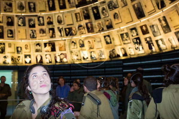 A female IDF Paratroopers officer looks upwards in The Hall of Names at Yad Vashem Holocaust Museum, at display of 600 photographs and fragments of Pages of Testimony. Jerusalem, Israel. 1st December 2011.