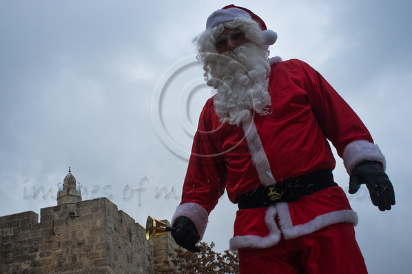 Man dressed as Santa Claus stands on ancient old city walls beneath the King David Citadel tower near the Jaffa Gate overlooking the city. Jerusalem, Israel. 21st December 2011.