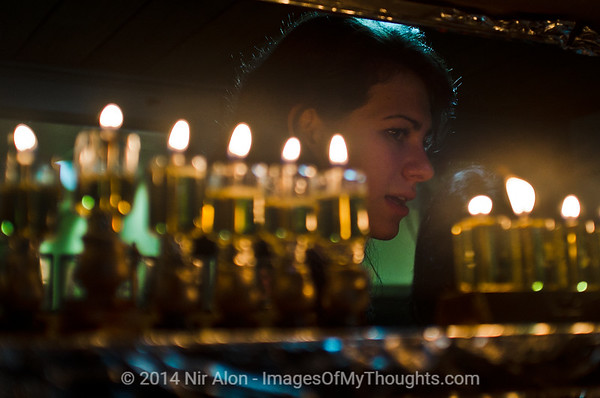 A young lady lights a chanukkiah, an eight-branched menorah, on the eighth and last night of the holiday of Chanukah. Jerusalem, Israel. 27th December 2011.