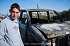 """Yusuf stands by his torched car, somewhat in awe at the results of an alleged, extremist-Jewish, arson attack in Bet Tzafafa. Attackers left the Hebrew word """"revenge"""" painted in red. . Jerusalem, Israel. 4th January 2012."""