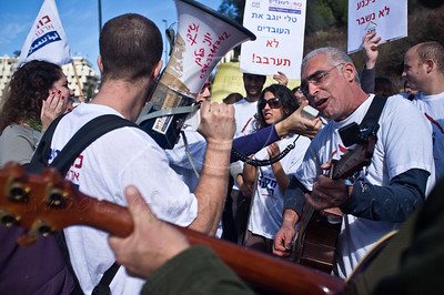 """Youth Protection Services worker plays and sings the """"Youth Protection Service Blues"""" at a protest for an increase in wages outside the Ministry of Social Affairs. Jerusalem, Israel. 10th January 2012."""