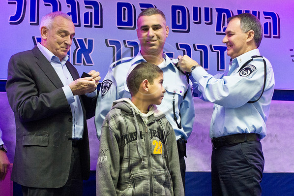 Minister of Internal Security Yitzhak Aharonovitch (L), Police Commissioner Yohanan Danino (R) award rank of Chief Superintendent to Yoram Barina at ceremony marking roll out of 2012 as 'Turning Point Year'. Jerusalem, Israel. 30th January 2012.