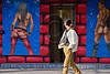 Archive photo – young woman passes by an erotic wall mural at entrance to a massage parlor in Tel-Aviv. Soliciting prostitution soon to impose prison sentences of up to six months. Jerusalem, Israel. 13th February 2012.