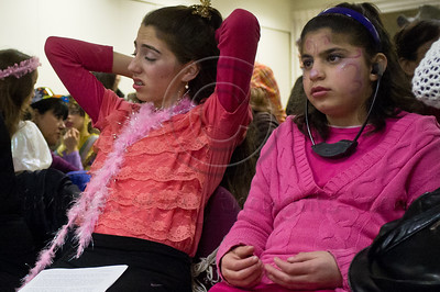 A young girl wears headphones with amplification in a special Purim reading of the Book of Esther for the deaf and hearing-impaired at Bet Zusman where use is made of special amplifiers, visual projection and simultaneous sign language translation. Jerusalem, Israel. 8-Mar-2012.