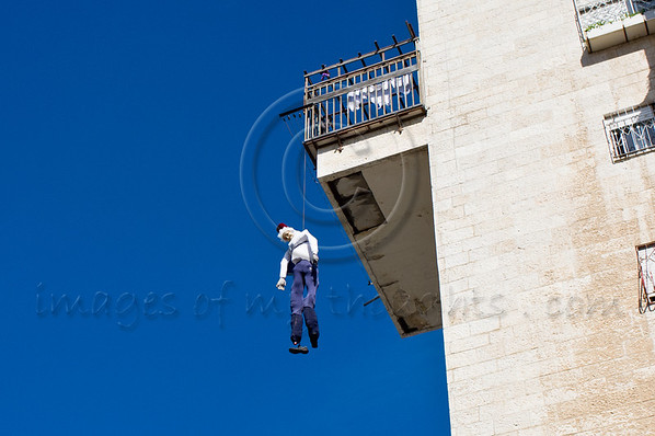 A figure of Haman hangs 'to death' from an eighth story balcony, symbolizing Haman's destiny as described in the Book of Esther, following his foiled attempt to massacre the Jews of Persia, as Purim is celebrated in the city. Jerusalem, Israel. 8-Mar-2012.