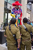 Two IDF soldiers look up to a clown on stilts on Purim, celebrated as a happy, carnival-like holiday, commemorating the events described in the Book of Esther and the foiled plot of Haman, Grand Vizier of the Persian Empire, to massacre the Jews. Jerusalem, Israel. 8-Mar-2012.