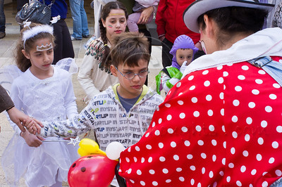A clown entertains children with balloons on Purim, celebrated as a happy, carnival-like holiday, commemorating the events described in the Book of Esther and the foiled plot of Haman, Grand Vizier of the Persian Empire, to massacre the Jews. Jerusalem, Israel. 8-Mar-2012.