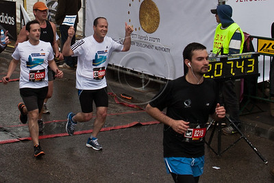 Jerusalem Mayor Nir Barkat, initiator of the International Marathon tradition in Jerusalem last year, gives the thumbs-up sign as he crosses the finish line of the 21Km half marathon with a respectable time of 02:07:43. Jerusalem, Israel. 16-Mar-2012.