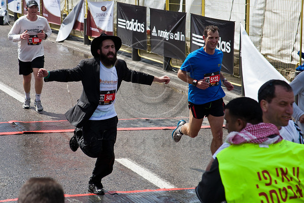 A Chasidic Jewish runner crosses the finish line of the 21Km Half Marathon in traditional clothing. Jerusalem, Israel. 16-Mar-2012.