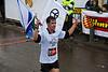 Runner number 7575, running for peace, crosses the finish line of the 21Km Half Marathon waving flags. Jerusalem, Israel. 16-Mar-2012.