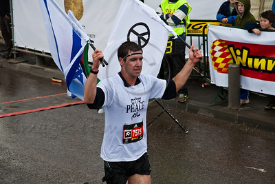 Runner number 7575, running for peace, crosses the finish line of the 21Km Half Marathon waving flags. Jerusalem, Israel. 16-Mar-2012.