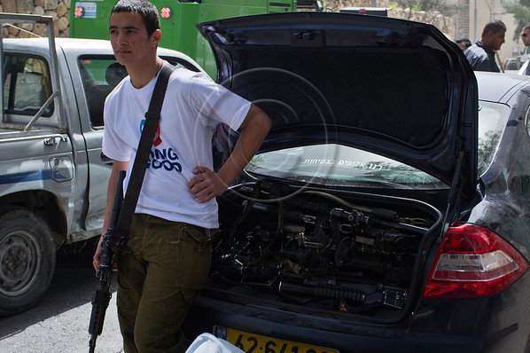 An IDF soldier of the Shachar Battalion keeps an eye on a trunk-full of M16 assault rifles as his colleagues paint the hallways of old residential buildings on Stern Street in Kiryat Yovel on 'Good Deeds Day'. Jerusalem, Israel. 20-Mar-2012.