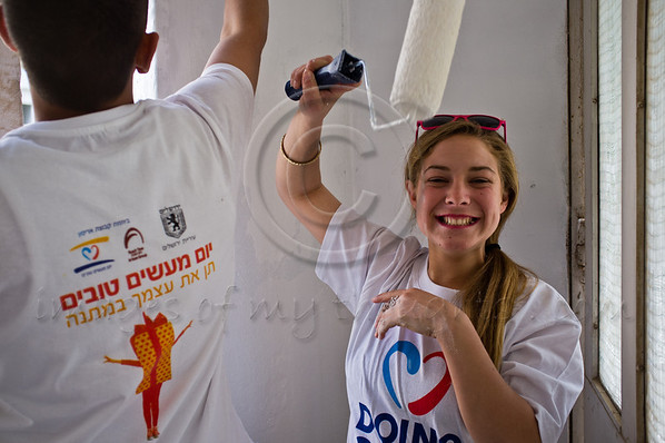 Female IDF soldier of the Shachar Battalion paints the hallways of old residential buildings on Stern Street in Kiryat Yovel on 'Good Deeds Day'. Jerusalem, Israel. 20-Mar-2012.