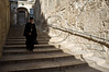 A lone priest descends the stairs leading to the Church of The Holy Sepulchre on Palm Sunday. Jerusalem, Israel. 1-Apr-2012.