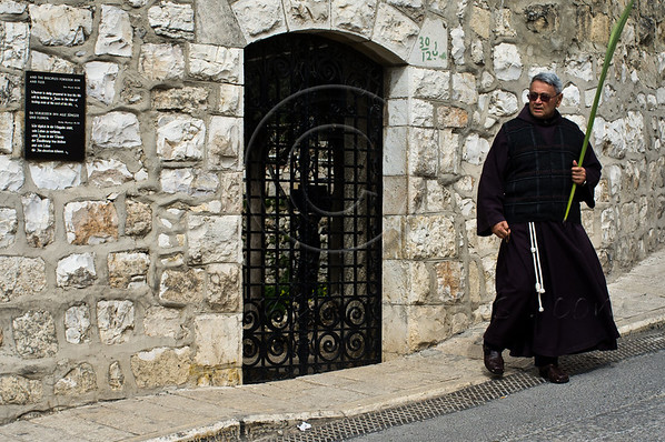 A priest carries a palm branch near the Church of All Nations awaiting the thousands scheduled to arrive with the Palm Sunday procession in celebration of Jesus' triumphant entry into Jerusalem. Jerusalem, Israel. 1-Apr-2012.