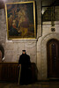 A nun stands below a painting of Jesus lowered from the cross after crucifixion in the Church of the Holy Sepulchre on Holy Thursday. Jerusalem, Israel. 5-Apr-2012.