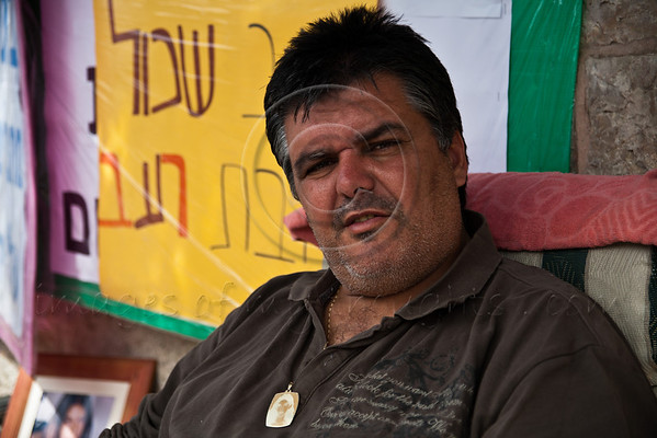 Kobi Sarusi, who lost his 14 year old daughter, Linoi Sarusi, to a terrorist attack in October 2002, wears a pendant engraved with daughter's picture and protests in a hunger strike opposite the PM's residence against Social Security Administration. Jerusalem, Israel. 5-Apr-2012.