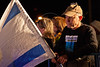 """Demonstrator at renewal of """"Draft For All"""" campaign opposite PM's office holds an Israeli flag and wears a sticker calling for equal distribution of burden of mandatory military service. Jerusalem, Israel. 21-Apr-2012."""