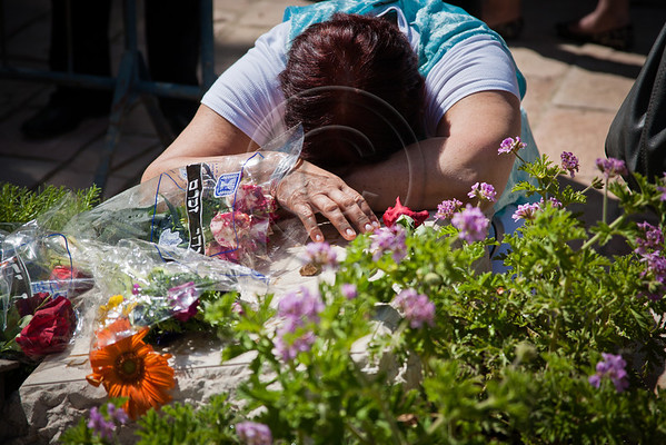 A mother lays her head in grief on the grave of her son in the Police section of Mt. Hertzl Military Cemetery. Jerusalem, Israel. 25-Apr-2012.