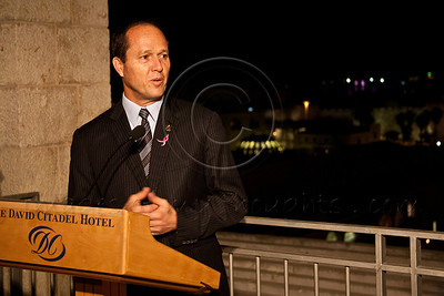 Jerusalem Mayor Nir Barkat, wearing a pink Komen emblem on jacket lapel, addresses the audience at Race for the Cure initiation overlooking the Old City walls soon to be illuminated in pink. Jerusalem, Israel. 1-May-2012.