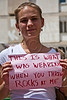 """A very modestly dressed young woman holds up a sign reading """"This is what I was wearing when you threw rocks at me"""". Jerusalem, Israel. 4-May-2012."""